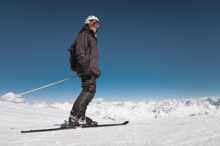 A bearded male skier in a helmet and a ski mask is standing on skis against the background of snow-capped mountains and a blue sky. Athlete in a black suit