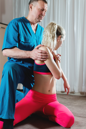 Male manual visceral therapist masseur treats a young female patient. Stretching the spine and intercostal system Stock Photo