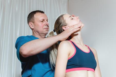 Männlicher manueller viszeraler Therapeut Masseur behandelt eine junge Patientin. Bearbeiten von Hals und Wirbel Standard-Bild