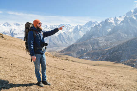 Bearded man in sunglasses and a hat with a backpack points hand at the mountains. Travel concept on the background of a mountain landscape