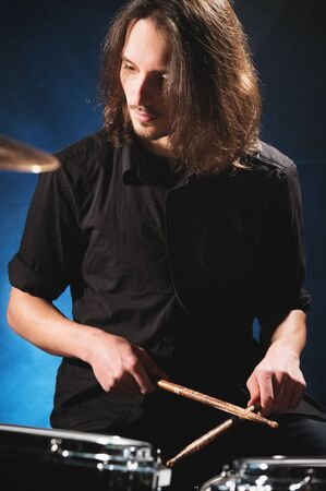 Portrait of a long-haired drummer with chopsticks in his hands sitting behind a drum set. Low key. Concepts of the creative freedom of the millenial generation