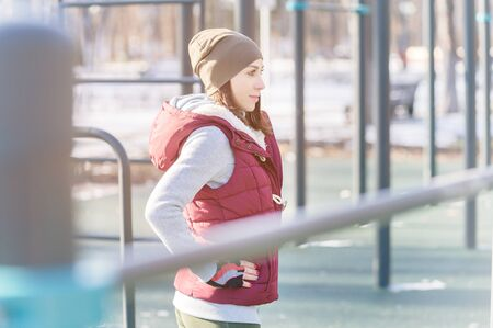 Portrait of a sports girl engaged in a workout in the winter on an outdoor sports field. Warm up