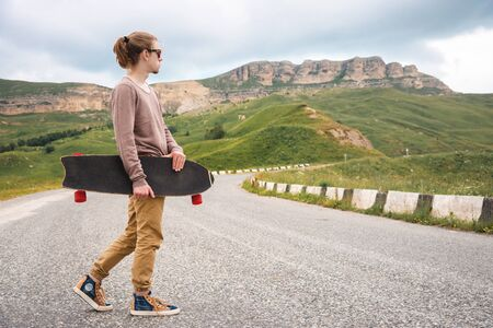 A stylish young man walks along a winding mountain road with a skate or longboard in his hands the evening after sunset. The concept of youth sports and travel hobbies