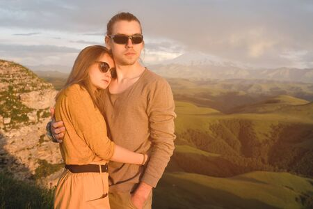 Portrait of a romantic young hipster couple hugging. They stand in an embrace in nature high in the mountains against the backdrop of a mountain green valley and clouds.