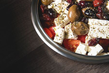 Close-up of delicious gourmet tomato and olives feta cheese salad sprinkled with spices of herbs. The concept of delicious and healthy vegetarian food and body detoxification