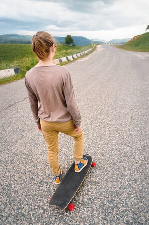 Young stylish man with long hair gathered in a ponytail and in sunglasses stands with a longboard on a country asphalt road in the mountains on the background of epic rocks 版權商用圖片 - 127926381