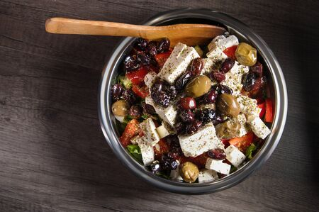 Close-up of delicious gourmet tomato and olives feta cheese salad sprinkled with herbs spices in a metal bowl. The concept of delicious and healthy vegetarian food and body detoxification Foto de archivo