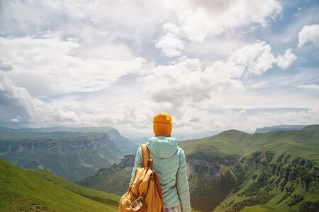 The view from the back of a tourist girl with a backpack is standing and looking at the mountain green valleys and plateau on a sunny day against the sky and clouds. Travel and tourism concept Stock Photo