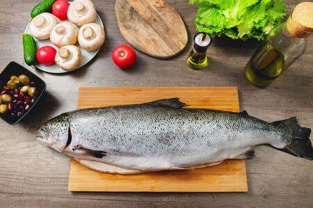 Primer plano de pescado keta, entero en la tabla de cortar de la mesa de la cocina junto a aceitunas, tomates y champiñones. Mariscos saludables. Cocina casera