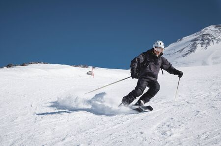 A bearded mature aged male skier in a black ski suit descends along the snowy slope of a ski resort amid two peaks of Mount Elbrus. The concept of sports in adulthood Foto de archivo - 127926663