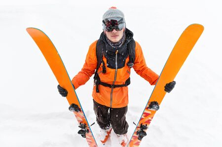 A professional skier athlete in an orange black suit with a black ski mask with skis in his hands stands with a displeased mass during a snowstorm on a light background in the snow Foto de archivo - 127926666