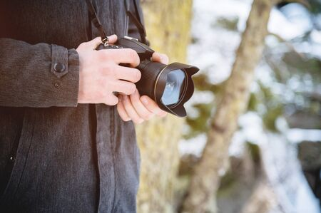 Close-up professional digital mirror camera in male hands in the winter forest. Photo travel concept Foto de archivo - 127926668
