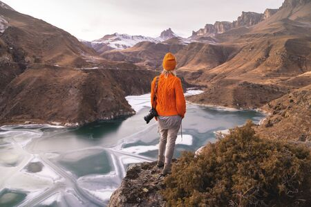 Portrait from the back of the girl traveler photographer in an orange sweater and hat with a camera in hand in the mountains against the background of a frozen mountain lake. Photo travel concept Foto de archivo - 127926743