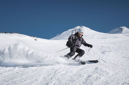 A bearded mature aged male skier in a black ski suit descends along the snowy slope of a ski resort amid two peaks of Mount Elbrus. The concept of sports in adulthood Foto de archivo - 127926748