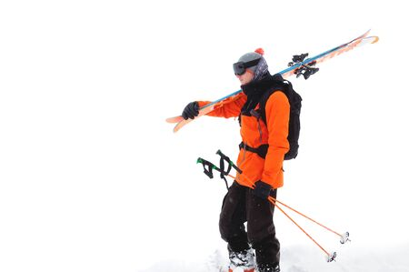 Portrait of a professional athlete skier in an orange jacket wearing a black mask and with skis on his shoulder looks into the camera. Isolated on white Foto de archivo - 127926749