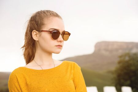 Portrait of a young attractive serious girl in sunglasses against the background of rocks and sky. Seriousness in the millenial generation Foto de archivo - 127926755