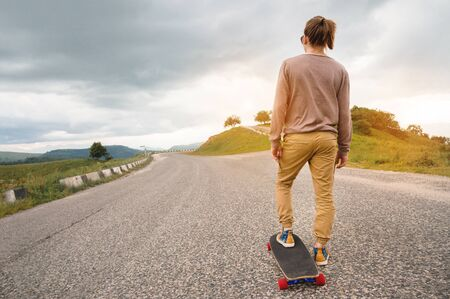 Young stylish man with long hair gathered in a ponytail and in sunglasses stands with a longboard on a country asphalt road in the mountains on the background of epic rocks