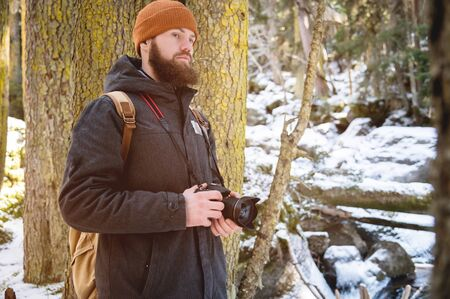 Portrait of a bearded photographer with a reflex camera in his hands in the winter coniferous forest. Photo travel concept Foto de archivo - 127927212