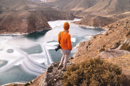 Portrait from the back of the girl traveler photographer in an orange sweater and hat with a camera in hand in the mountains against the background of a frozen mountain lake. Photo travel concept Foto de archivo - 127927215