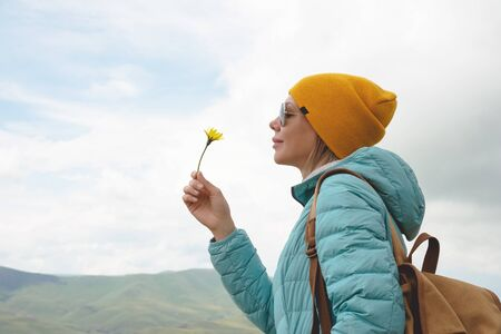 Portrait of a girl in a hat and sunglasses is holding a flower in early spring on nature. The concept of unity with nature Foto de archivo - 127927219