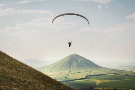 A paraglider flies in the sky in a cocoon suit on a paraglider above the mountain on a sunny summer day. Paragliding Sport Concept. Foto de archivo - 127927228