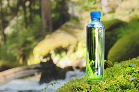Plastic bottle blue cap with fresh drinking water on a background of green forest stands on a stone with moss. The concept of pure natural mountain water Banco de Imagens