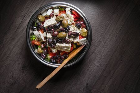 Close-up of delicious gourmet tomato and olives feta cheese salad sprinkled with herbs spices in a metal bowl. The concept of delicious and healthy vegetarian food and body detoxification Stockfoto