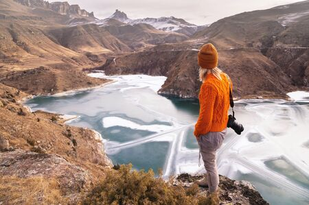Portrait from the back of the girl traveler photographer in an orange sweater and hat with a camera in hand in the mountains against the background of a frozen mountain lake. Photo travel concept