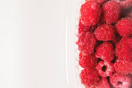 Close-up ripe juicy and delicious raspberry in a plastic transparent dish on a light background. Saturated healthy fresh food