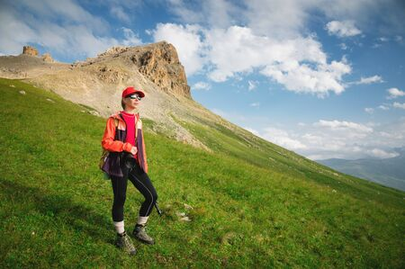 Girl athlete photographer in a red cap sunglasses and a yellow backpack stands on a green slope against the background of the epic cliffs of the Caucasus 写真素材