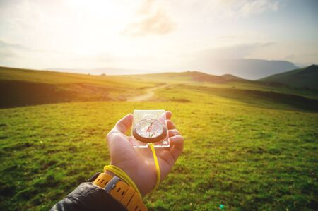 Male hand with a magnetic compass ea against the backdrop of a beautiful landscape at sunset. The concept of navigating the search for your own path and orientation to the cardinal points Stockfoto