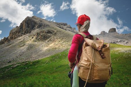 View from the back Girl athlete in a red cap sunglasses and a yellow backpack stands on a green slope against the background of the epic cliffs of the Caucasus