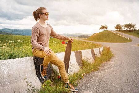 Young stylish man with long hair in sunglasses is sitting on a chipper with a longboard in his hands on a country asphalt road on background of rocks and clouds