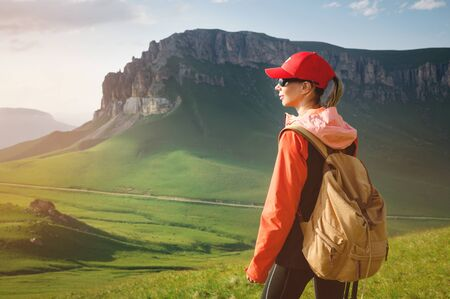 Girl athlete in a red cap sunglasses and a yellow backpack stands on a green slope against the background of the epic cliffs of the Caucasus 写真素材