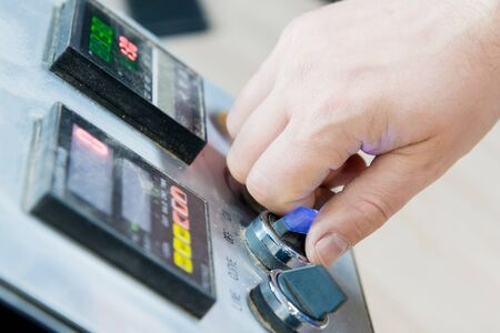 Close-up of a male hand on a dashboard controlling production equipment with buttons and displays in a locksmiths workshop for furniture production