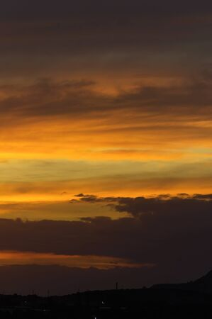 Abstract nature background. Dramatic sunset sky in the clouds saturated with bright colors of orange and yellow. Contrast Low Key 写真素材