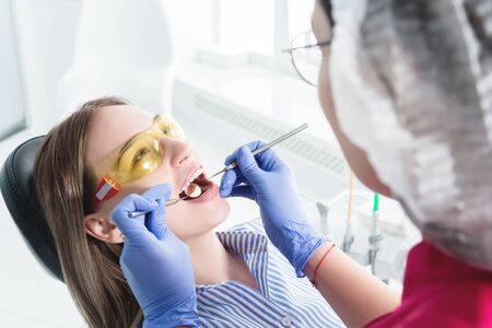 In the dentists office. A female dentist in glasses is preparing to make a cast of the jaw of a young girl patient. Care clean mouth