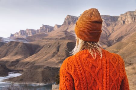 Portrait from the back of the girl traveler in an orange sweater and hat in the mountains against the background of a frozen mountain. Photo travel concept