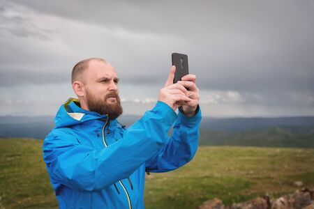 A bearded man takes photos or videos outdoors on his smartphone. A guy in a jacket on a background of mountain valleys and a gray sky weedt broadcast on the phone
