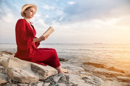 An attractive Caucasian girl in a red bright dress and a straw hat sits on a large stone by the sea at sunset and reads an interesting book on the sea horizon and beautiful clouds.