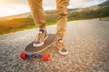 Close-up of male legs in rag sneakers on a longboard on the background of asphalt at sunset. Big skateboard with man legs. Youth leisure concept Stockfoto