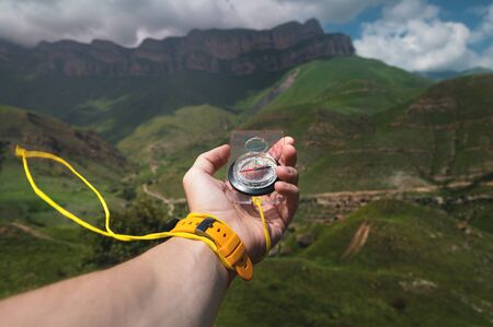 Close-up wide angle male hand with a yellow watch bracelet holds a magnetic navigation compass against the backdrop of a beautiful landscape in the mountains