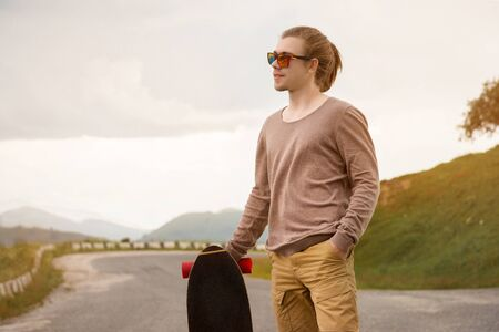 Stylish young man standing along a winding mountain road with a skate or longboard on his shoulder in the evening after sunset. The concept of youth sports and travel hobbies