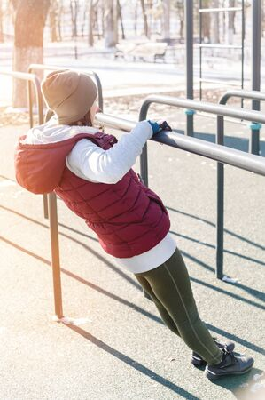 Portrait of a sports girl doing workout in the winter on an outdoor sports field. Exercises on Uneven Bars