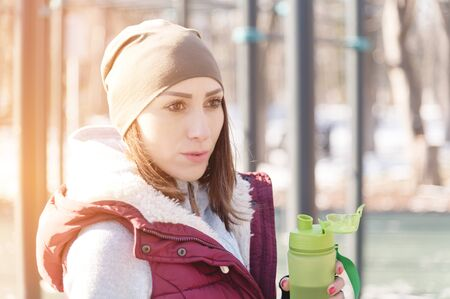 Portrait of a sports girl engaged in a workout in the winter on an outdoor sports field. Drinks water quenches thirst