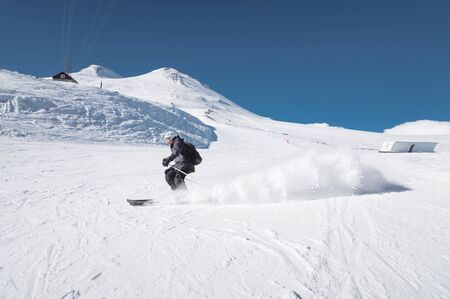 A bearded mature aged male skier in a black ski suit descends along the snowy slope of a ski resort amid two peaks of Mount Elbrus. The concept of sports in adulthood