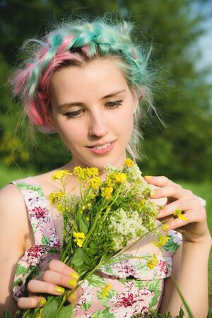 Portrait of a young happy smiling girl in a cotton dress with a bouquet of wildflowers