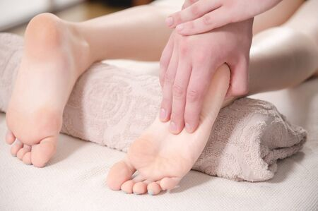 Close-up Relaxing foot massage at the spa. Male hands knead the female foot. Body care concept