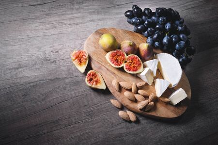 Still life cheese plate on a wooden cutting board lies sliced cheese with mold almonds in the shell and sliced figs next to a bunch of black grapes. Delicious and healthy food concept