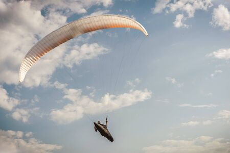 A paraglider flies in the sky in a cocoon suit on a paraglider against the sky and clouds. Paragliding Sport Concept